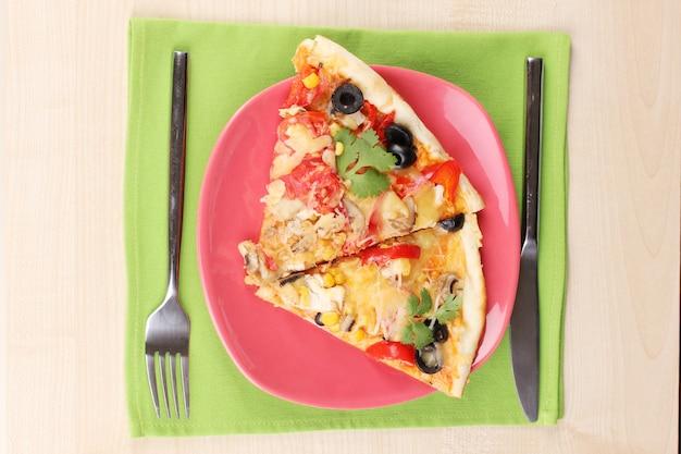Deliziosa fetta di pizza sul primo piano piatto di colore sulla tavola di legno
