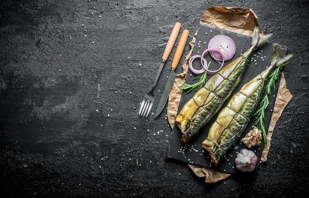 Delizioso pesce sgombro affumicato con anelli di cipolle fresche e spicchi d'aglio. sulla tavola rustica nera
