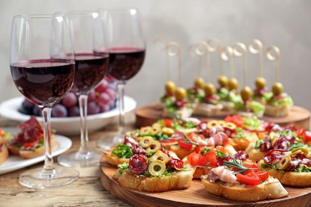 Deliziosi snack e vino rosso serviti sul tavolo