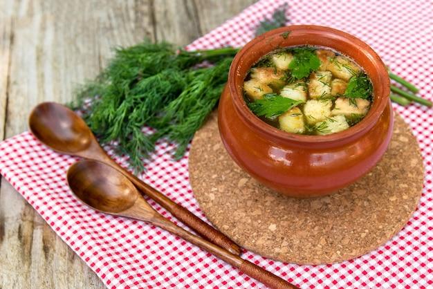 Deliziosa zuppa con crostini di pane e pollo in una pentola di terracotta.