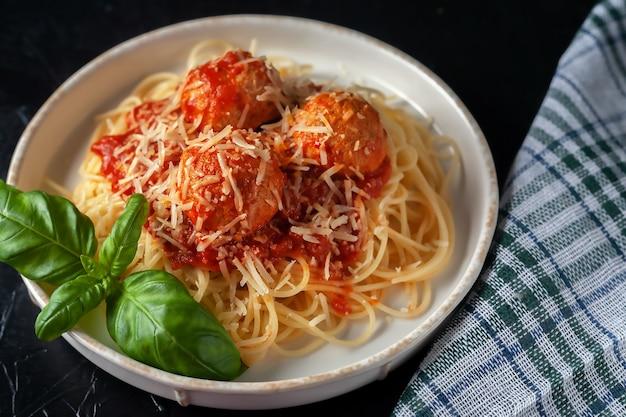 Deliziosi spaghetti con polpette, parmigiano e salsa di pomodoro in un piatto