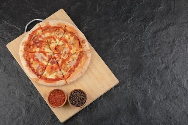 Deliziosa pizza piccante di pollo di bufala e condimenti su tavola di legno.