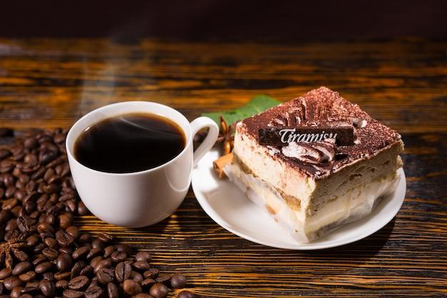 Deliziosa fetta di torta a forma quadrata nel piatto accanto alla tazza piena di caffè circondata da fagioli scuri su sfondo di legno macchiato