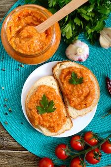 Delizioso caviale di zucca in un barattolo e spalmato su fette di pane bianco sul tavolo. caviale fatto in casa con zucchine, aglio, carote, salsa di pomodoro. cucina vegana. la vista dall'alto disteso