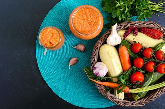 Caviale di zucca delizioso in un barattolo sul tavolo. caviale fatto in casa con zucchine, aglio, carote, salsa di pomodoro. cucina vegana. la vista dall'alto disteso