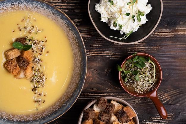 Deliziosa zuppa di crema di zucca e zucca decorata con crostini di pane, formaggio e microgreens su uno sfondo di legno scuro, zuppa di purea vegetariana, cibo sano.