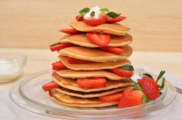 Deliziosa pila di pancake con fragole e crema di close-up