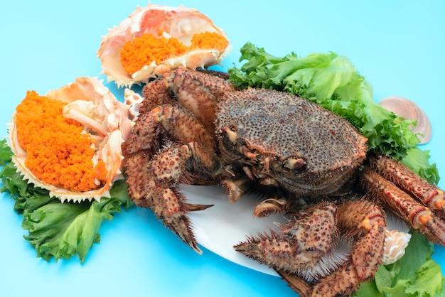 Delizioso granchio al vapore si trova su un piatto bianco su sfondo blu con caviale di granchio arancione e insalata verde