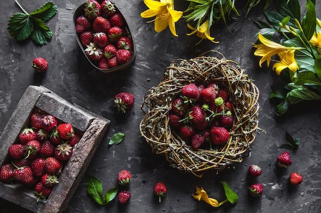 Deliziose fragole con fiori gialli su un grigio scuro in una ghirlanda vintage. cibo sano, frutta