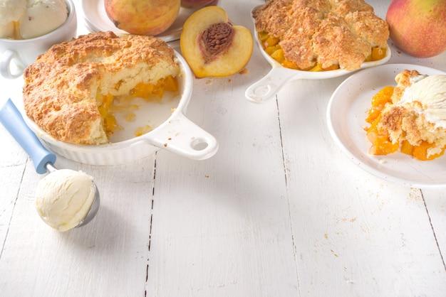 Deliziosa estate peach cobbler, dolci fatti in casa estate torta con pesche e gelato alla vaniglia su bianco sullo sfondo di legno spazio copia