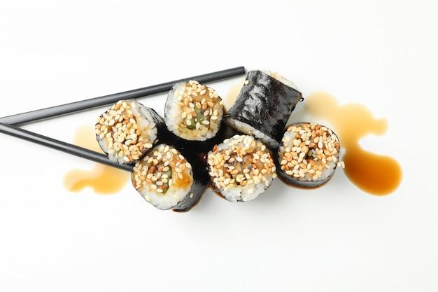 Rotoli di sushi, soia e bastoncini deliziosi su superficie bianca
