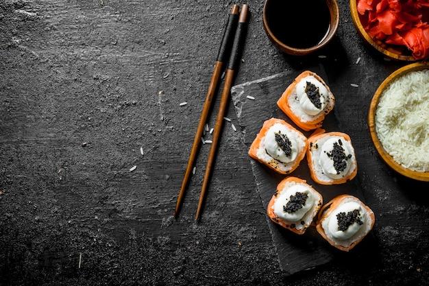 Deliziosi involtini di sushi con salmone su supporto in pietra e salsa di soia. sulla tavola rustica nera