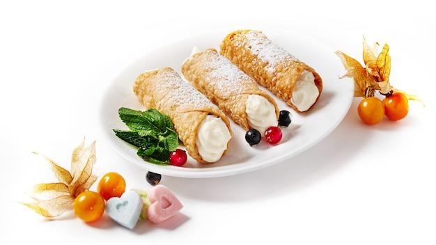 Deliziosi cannoli dolci con frutti di bosco su uno sfondo bianco isolato.