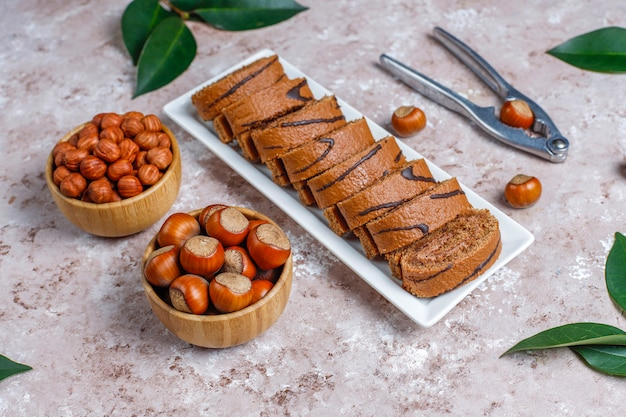 Rotolo delizioso del dolce di cioccolato con la crema della nocciola e le nocciole, vista superiore