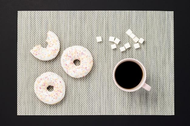 Ciambelle deliziose, dolci, fresche, una tazza di caffè, sfondo nero. concetto di colazione, fast food, caffetteria, panetteria, pranzo. vista piana, vista dall'alto.