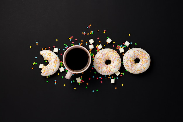 Ciambelle deliziose, dolci, fresche, caramelle decorative multicolori, una tazza di caffè su sfondo nero. concetto di colazione, fast food, caffetteria, prodotti da forno. vista piana, vista dall'alto.