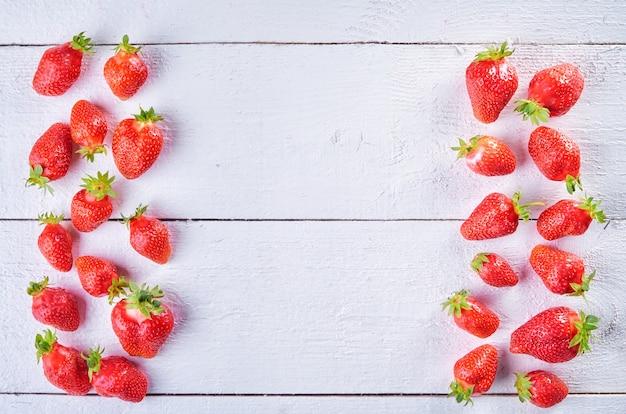 Delizioso mix di frutta dolce di fragola sul tavolo in legno bianco wintage. sfondo di frutta brillante.