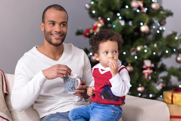 Dolci deliziosi. dolce adorabile giovane ragazzo che tiene un marshmallow e lo mangia mentre è seduto sulle gambe di suo padre