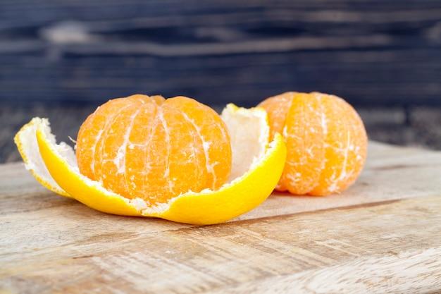 Deliziosi mandarini, buccia d'arancia sbucciata adagiata su un tavolo di legno, agrumi sani e ricchi di vitamine