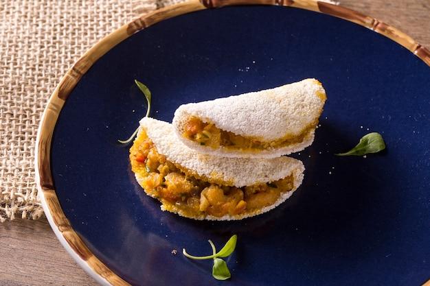 Delicious tapioca, uno spuntino brasiliano a base di farina di manioca e gamberetti, manioca su un piatto blu