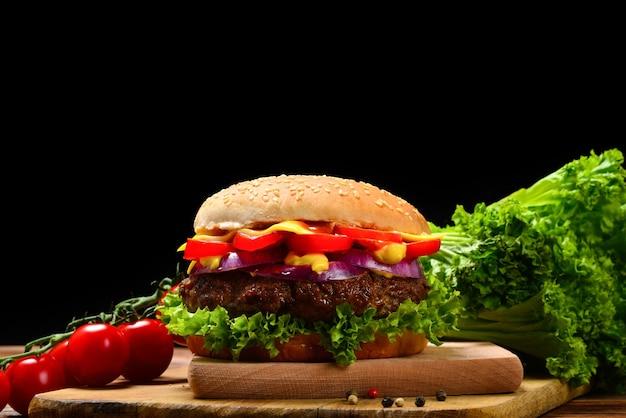Delizioso hamburger gustoso con carne di manzo, pomodori, insalata e salsa sul tavolo di legno e sfondo nero. spazio per testo o design.