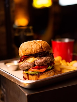 Hamburger fatto in casa alla griglia gustoso delizioso con carne di manzo, formaggio, pancetta e salsa su un tavolo di legno con spazio per copia. mani che tengono hamburger con patatine fritte e birra. gruppo di amici che mangiano fast food