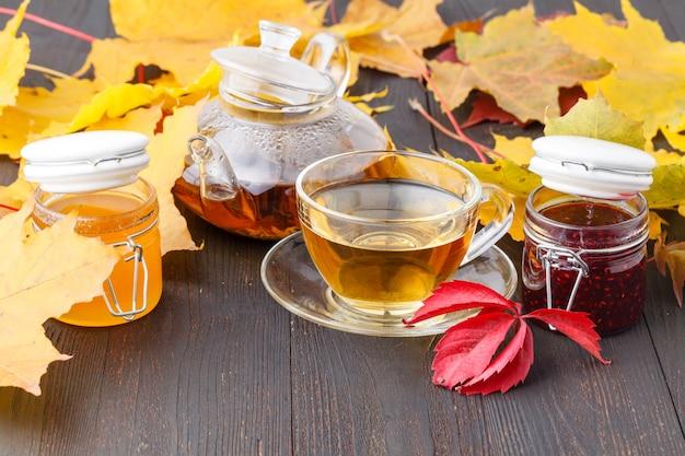Delizioso tè con bacche di olivello spinoso in tazza di vetro sul tavolo