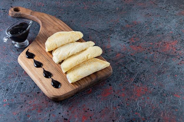 Deliziose frittelle sottili e sciroppo di cioccolato su tagliere di legno.