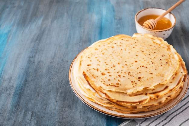 Deliziosi pancakes sottili miele. spazio per il testo