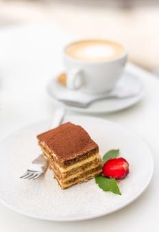 Deliziosa torta tiramisù con fragole fresche e menta su un piatto su sfondo bianco. colazione con una tazza di caffè al bar