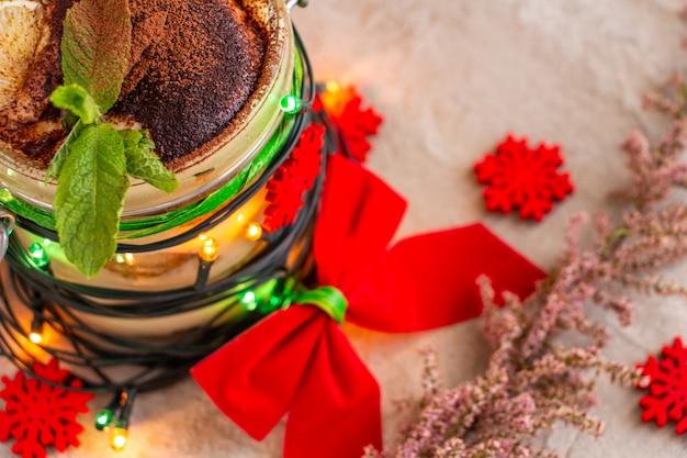 Delizioso tiramisù spolverato di cacao con un rametto di menta decorato per le luci di natale fiocco rosso...