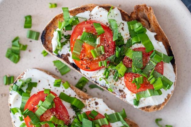 Delizioso pane tostato con crema di formaggio bianco, aglio selvatico verde e pomodoro rosso sulla piastra, da vicino