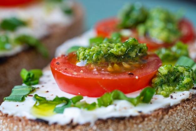 Delizioso pane tostato con crema di formaggio bianco, aglio selvatico verde e pomodoro rosso su piatto, primo piano