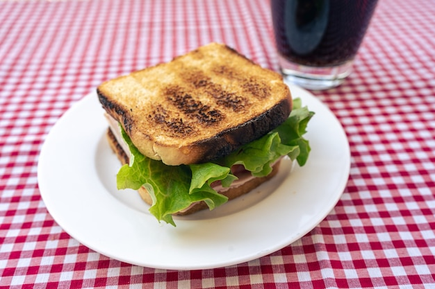 Delizioso panino con prosciutto tostato, pomodoro e lattuga.