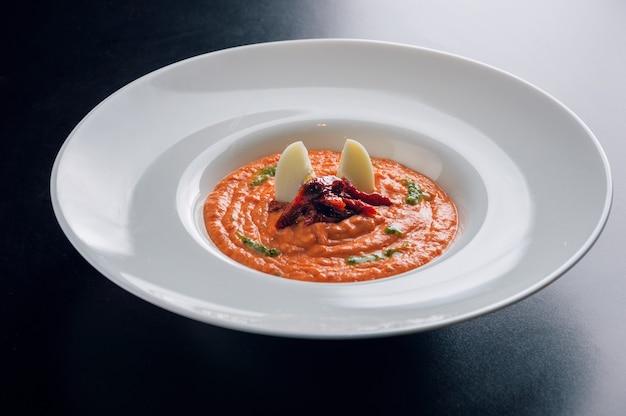 Deliziosa zuppa di pomodoro con pomodori secchi e uova di quaglia servita in un piatto fondo