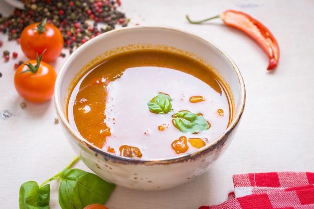 Deliziosa zuppa di pomodoro con carne in una ciotola bianca su un tavolo di legno con pomodorini freschi