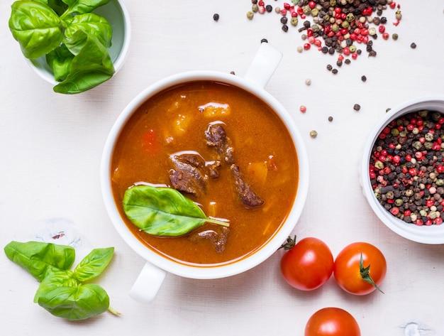 Deliziosa zuppa di pomodoro con carne su un tavolo in legno rustico bianco con pomodorini freschi, foglie di basilico e pepe secco. ingredienti per la zuppa. vista dall'alto Foto Premium
