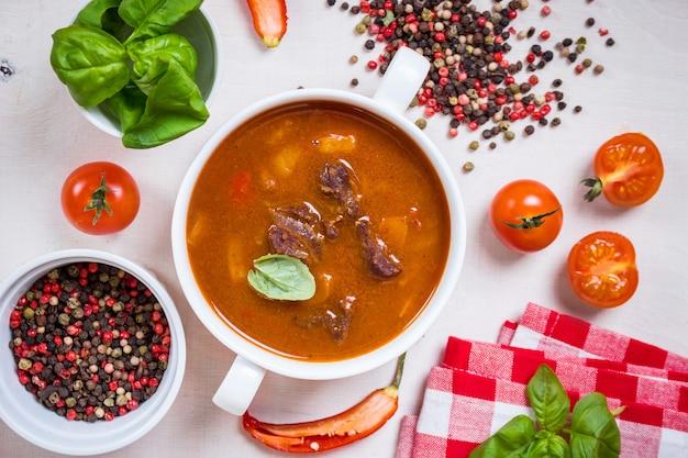 Deliziosa zuppa di pomodoro con carne su un tavolo in legno rustico bianco con pomodorini freschi, foglie di basilico e pepe secco. ingredienti per la zuppa. vista dall'alto