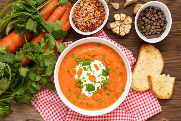 Deliziosa zuppa di carote tradizionale con erbe e panna acida. vista dall'alto.
