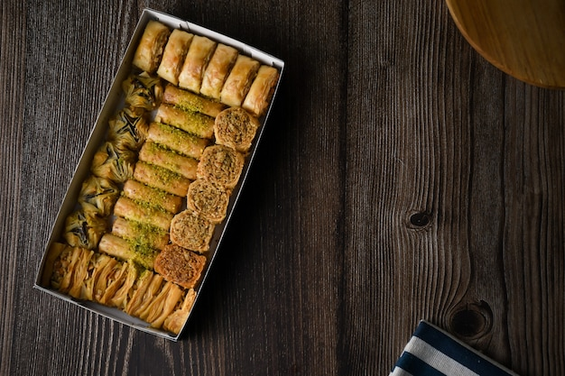 Deliziosa pasticceria turca baklava con miele su vassoio in legno sfondo alimentare