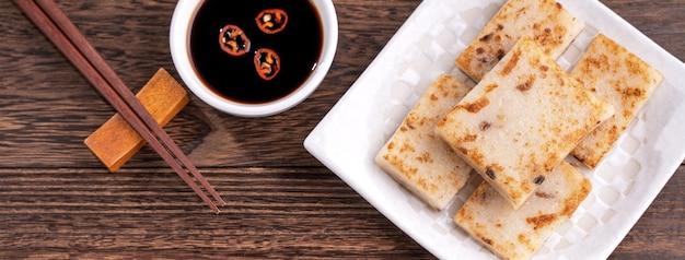 Deliziosa torta di rape, torta di ravanello tradizionale cinese nel ristorante con salsa di soia per i piatti di capodanno, primo piano, spazio copia, vista dall'alto, piatto.