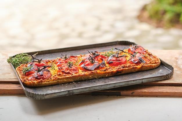 Deliziosa pizza vegetariana con pomodori in teglia