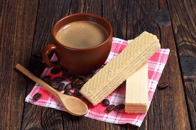 Deliziosi wafer e tazza di caffè caldo per colazione sul tavolo di legno scuro