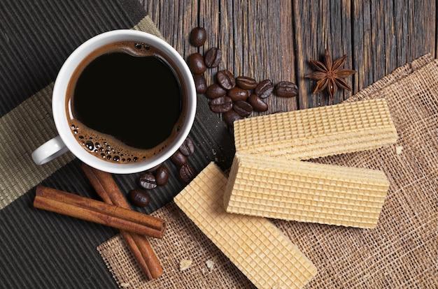 Deliziose cialde e tazza di caffè caldo per colazione su tavola in legno rustico