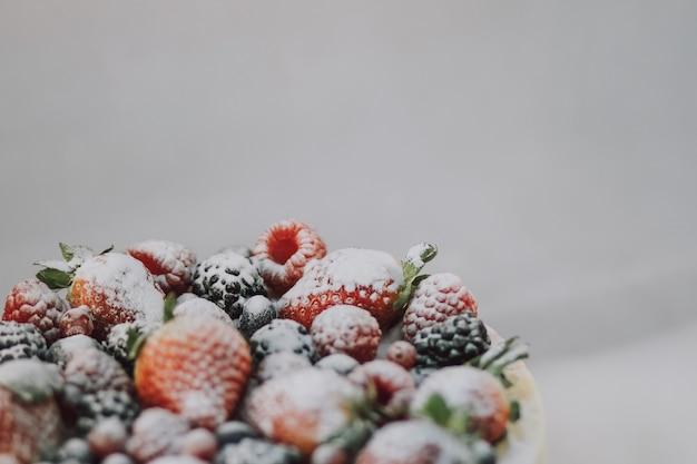 Deliziosa torta bianca con frutti naturali e polvere bianca in cima su sfondo bianco