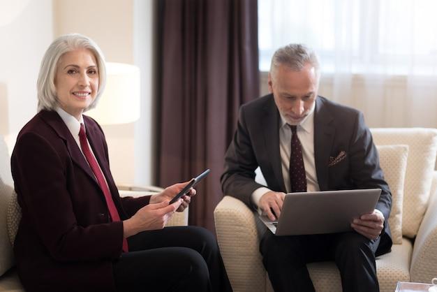 Felicissimo del lavoro. donna di affari invecchiata felice allegra che sorride e che tiene il tablet mentre era seduto in ufficio vicino al collega con il laptop e lavorava insieme al progetto