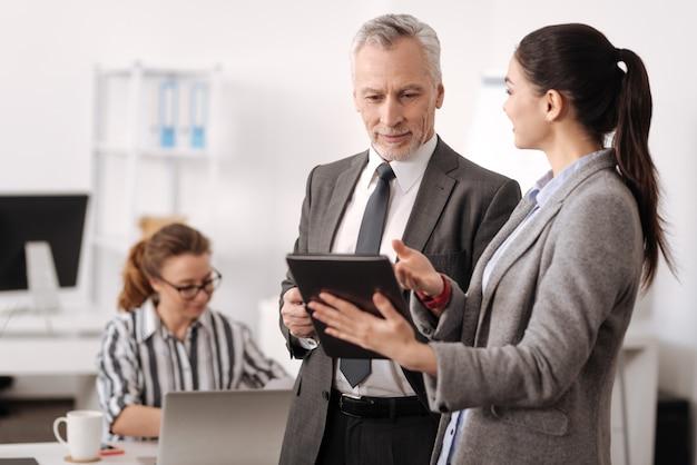 Felice l'uomo negli anni in piedi vicino al giovane collega guardando lo schermo del tablet mentre pensa alla futura conferenza