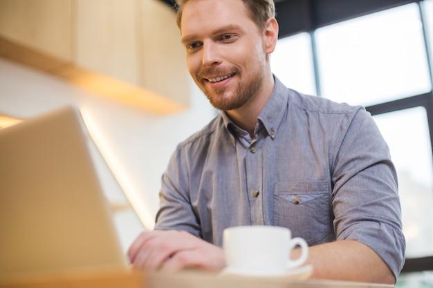 Felice simpatico uomo gioioso guardando lo schermo del laptop e sorridente pur essendo di umore positivo