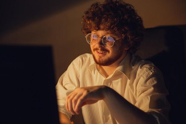 Felice e stanco. uomo che lavora in ufficio da solo durante la quarantena covid-19, rimanendo fino a tarda notte. giovane uomo d'affari, manager che svolge attività con smartphone, laptop, tablet in un'area di lavoro vuota.