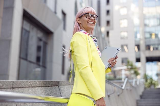 Donna contentissima con il computer portatile che sorride alla scalinata della strada
